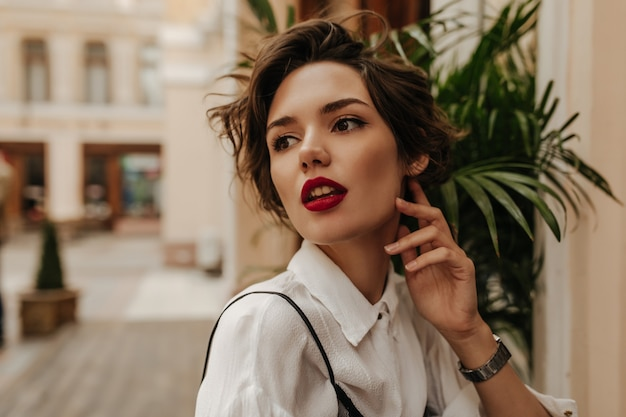 Curly woman with bright red lipstick looking way in restaurant. wonderful woman with brunette hair in white clothes posing in cafe.