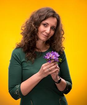 黄色の背景にクロッカスの花と巻き毛の女性