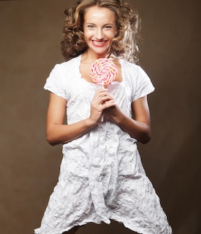 Curly woman with lollipop over brown background