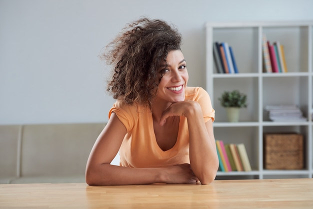 Curly young caucasian brunette sitting at table at home and smiling for camera