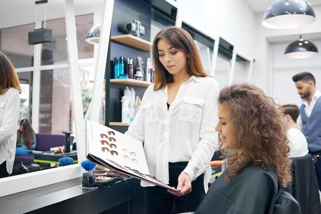巻き毛サロンに座っている髪の調子を整える色を巻き毛の若い女の子。