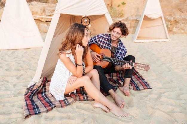 Кудрявый молодой человек играет на гитаре для своей подруги, сидя в палатке для кемпинга