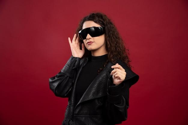 Giovane donna riccia con gli occhiali neri.
