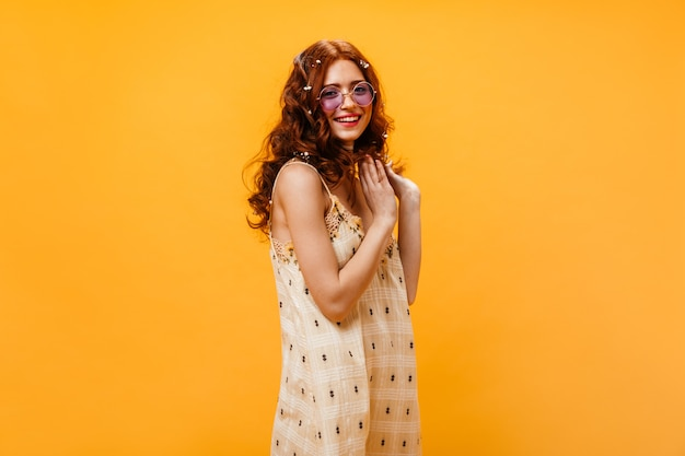 Curly young woman dressed in checkered summer dress and sunglasses posing on orange background.