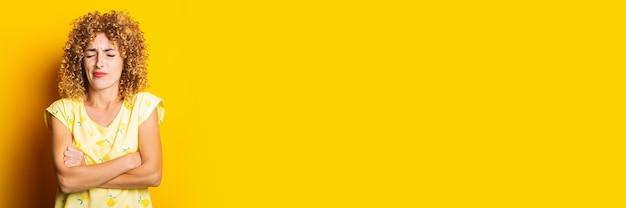 黄色の背景に交差した腕で顔をゆがめた巻き毛の若い女性