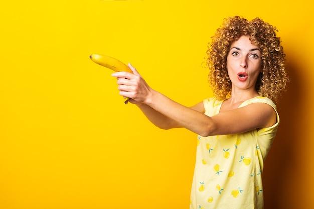 노란색 바탕에 권총처럼 바나나를 들고 곱슬 젊은 여자.