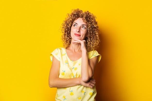 巻き毛の若い女性は彼女のあごの下で彼女の手を握って黄色の背景に思慮深く上向きに見えます