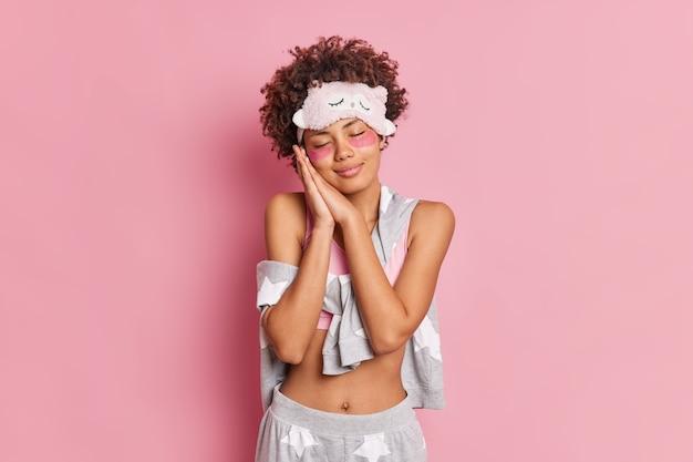 곱슬 젊은 여자 얼굴 근처에 손바닥을 유지 뭔가에 대한 눈의 꿈을 닫습니다 수면 마스크를 착용 캐주얼 파자마는 분홍색 벽에 고립 달콤한 꿈을 본다