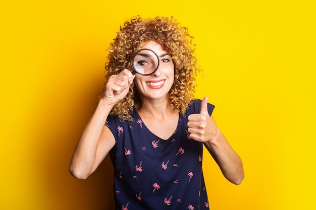 Curly young woman looking at camera through magnifying glass showing thumbs up gesture on yellow surface