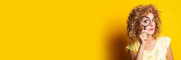 곱슬 젊은 여자는 노란색 표면에 돋보기를 통해 보이는