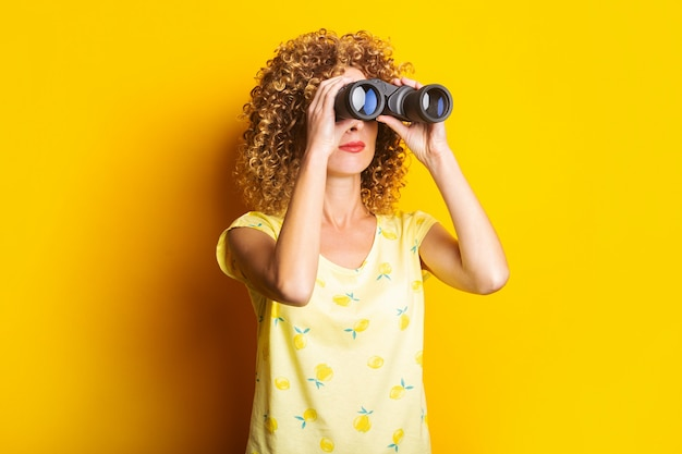 Curly young woman looks through binoculars on a bright yellow surface