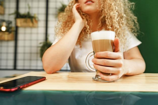 Кудрявая молодая женщина, сидящая за столом в кафе и расслабляющаяся с чашкой кофе, портрет