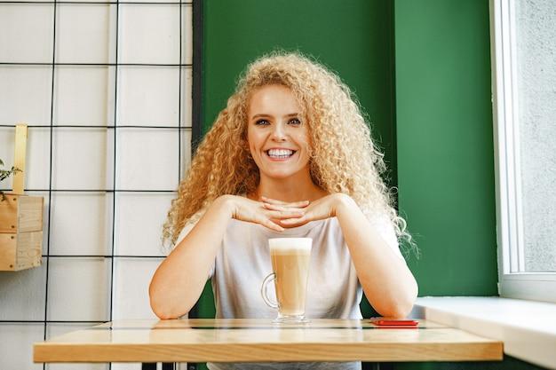 コーヒーショップのテーブルに座って、コーヒーを飲みながらリラックスする巻き毛の若い女性