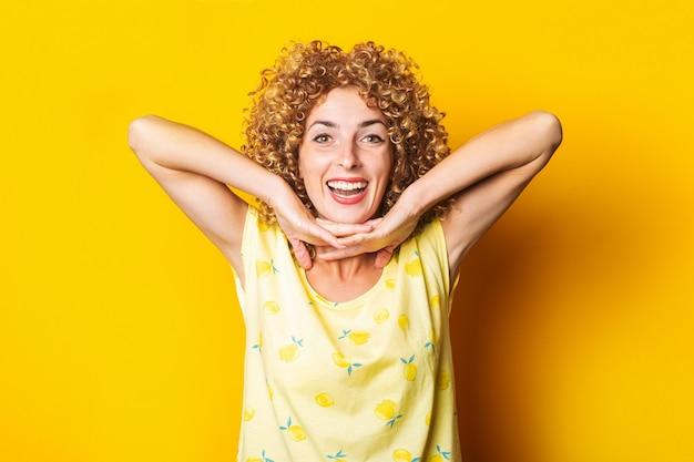 笑顔の巻き毛の若い女性は黄色の背景のあごの下に手のひらを保持します。