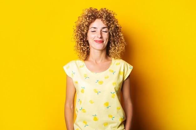 黄色の背景に目を閉じて笑っている巻き毛の若い女性