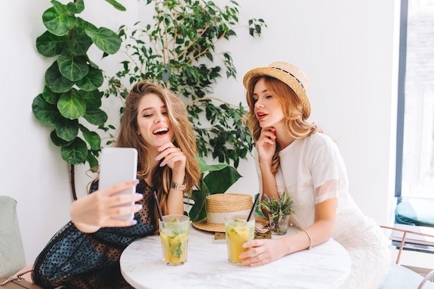 Curly young woman in straw hat holding glass of icy cocktail while her long-haired friend making selfie