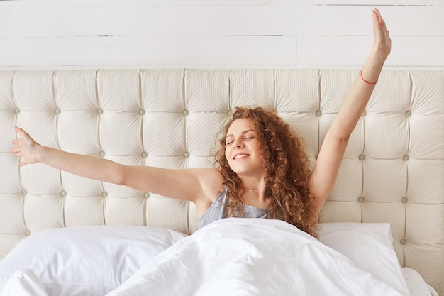 Curly young woman stretches her arms in cozy bed