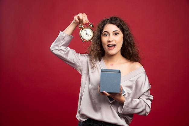 Giovane donna riccia che cattura orologio dalla confezione regalo.