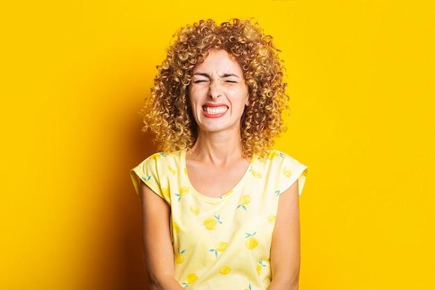 目を閉じて黄色の背景に顔をゆがめた巻き毛の若い女性