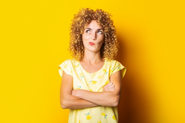 腕を組んで巻き毛の若い女性は、黄色の背景に思慮深く上向きに見えます