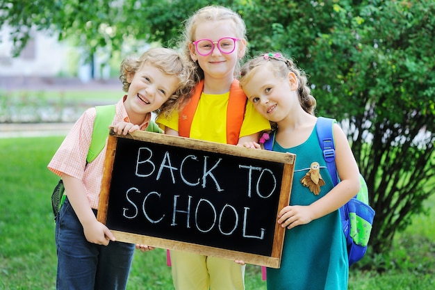 A curlyhaired boy and two girls with school bagssmile and hold a sign that says back to school