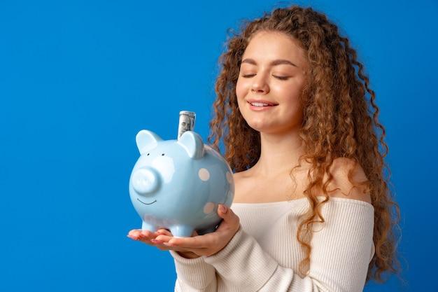 Кудрявая молодая женщина, держащая копилку на синем фоне