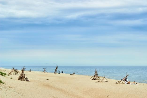 Curonian spit, russia-august 21, 2020. 사람들은 야생 해변에서 가족과 함께 휴식을 취합니다. 해변 wigwam