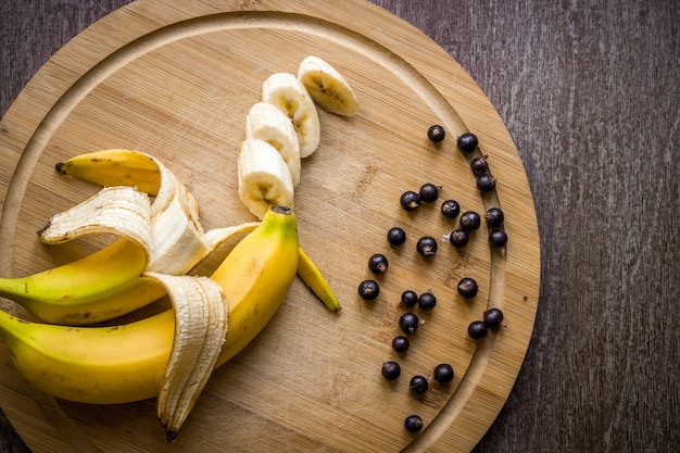 Currants and fresh banana on wooden table