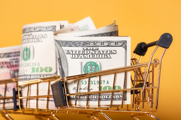 Currency, a cart of gold color with dollars in it on a yellow background. finance concept.