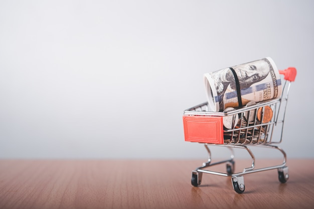 The currency coin is in a shopping cart that is placed on a wooden floor.