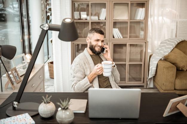 현재 질문. 쾌활한 긍정적 인 사람이 휴대 전화로 이야기하고 그의 캐비닛에서 뜨거운 차를 마시는