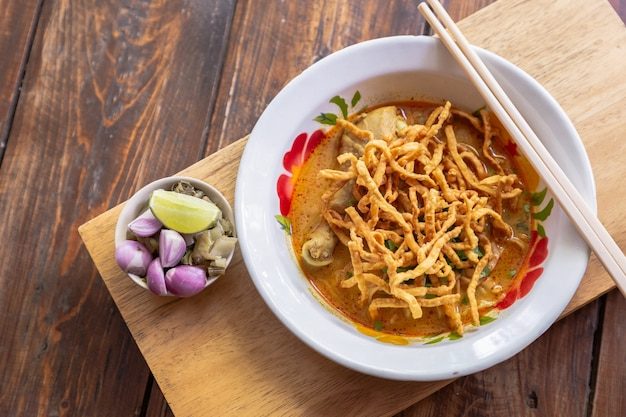 Curried noodle soup (khao soi) with chicken meat and spicy coconut milk on wood table.