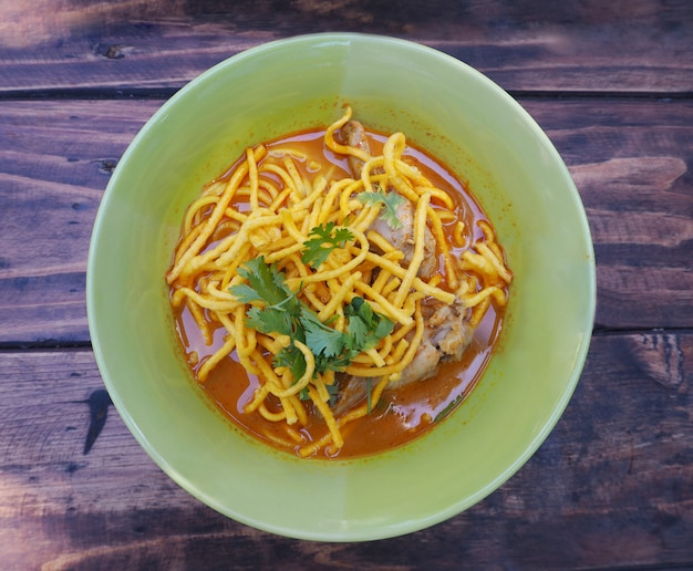 Curried noodle soup with chicken (khao soi) in green bowl on wood table
