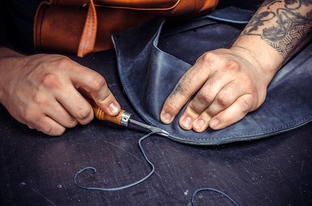 Курьер из кожи создает качественные изделия из кожи в своей дубильной мастерской.