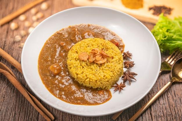 Курица карри с желтым рисом на тарелке над деревянным столом, курица с рисом басмати.