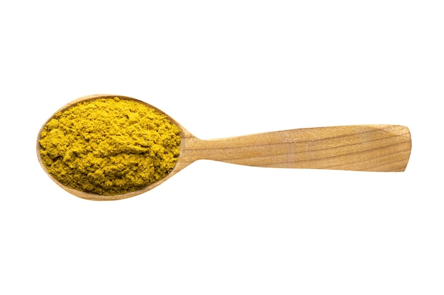 Curry powder for adding to food spice in wooden spoon