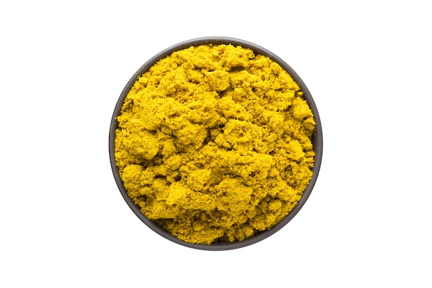 Curry powder in clay bowl isolated on white background