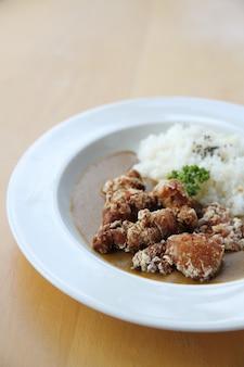 Рис карри с жареной курицей на фоне дерева