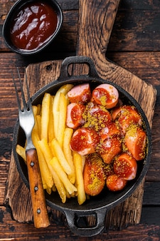 Currywurst sausages with curry spice on wursts served french fries in a pan. dark wooden table. top view.