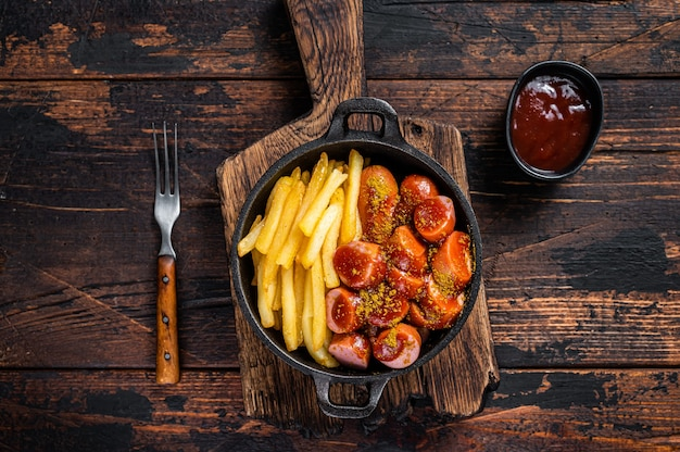 Currywurst street food meal, curry spice on wursts served french fries in a pan. dark wooden table. top view.
