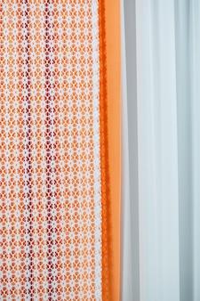 Образцы штор, висящие на вешалках на рельсах в магазине. выбор образцов текстуры ткани ткани для внутренней отделки шторы, тюль и обивка мебели.