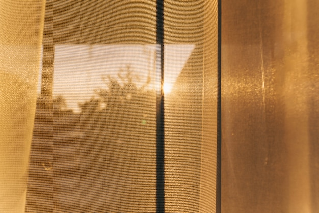 Curtains on window with sun.