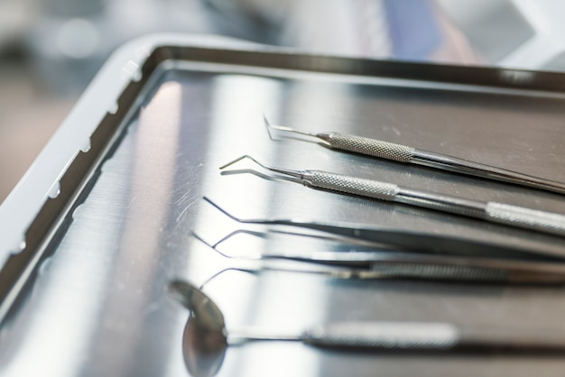 Профессиональные стоматологические инструменты в стоматологическом кабинете: зеркало для стоматолога, изогнутые щипцы, curv curler
