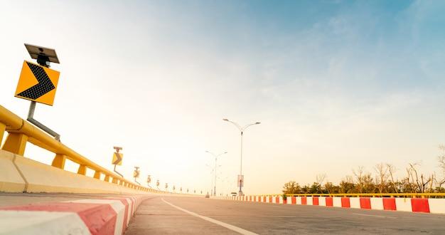 Кривая бетонная дорога с криволинейным дорожным знаком на берегу моря во время заката. энергия панели солнечных батарей на знак движения желтой кривой. поездка на летние каникулы. размытие за рулем автомобиля. летнее путешествие на машине.