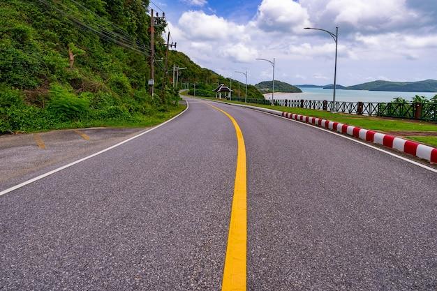 タイのプーケット島の熱帯海近くのカーブした道路。