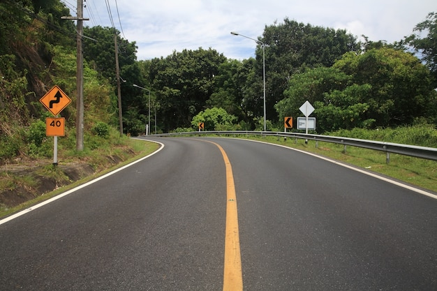 Curve uphill road and yellow street zigzag sign with 40 miles speed limit.