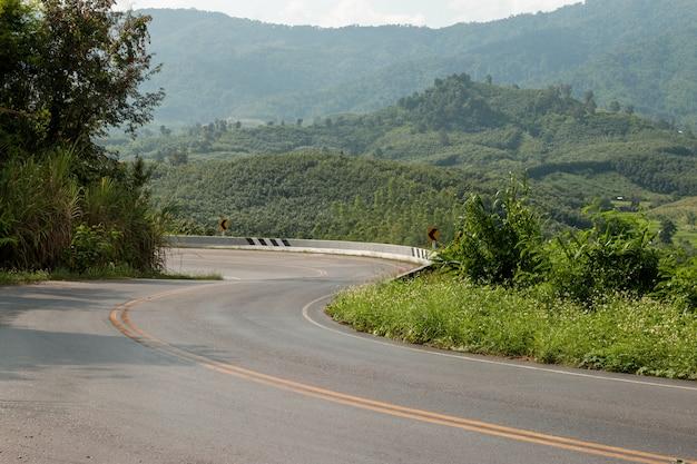 Изогнутая асфальтовая дорога на горе, концепция путешествия
