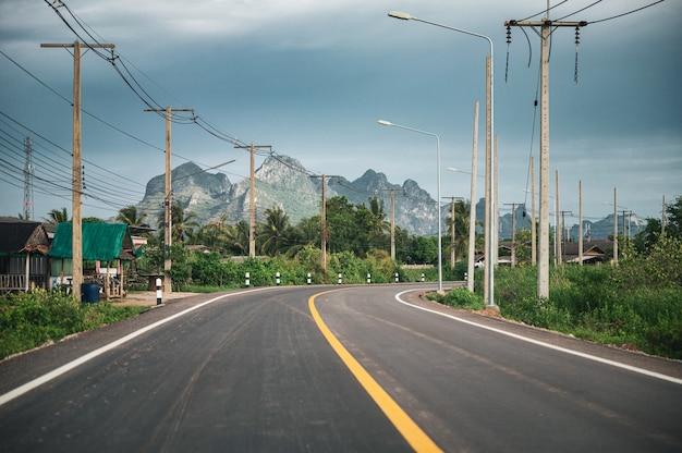 Prachuap khiri khan, sam roi yot의 시골에 있는 산맥, 전신주, 가로등 기둥이 있는 곡선 아스팔트 도로