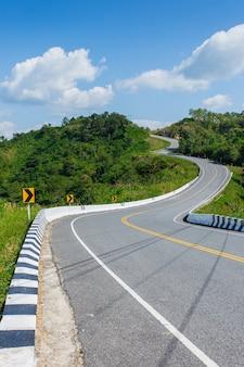 Изогнутая асфальтовая дорога с кривыми знаками в горах. провинция нан, таиланд