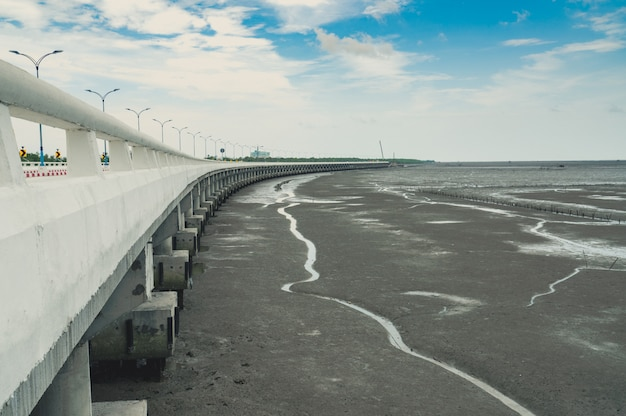 Curved coastal concrete highway road with lower water in the mud beach with blue sky